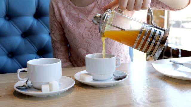 Mujer-joven-vierte-té-de-frutas-en-tazas-en-un-café