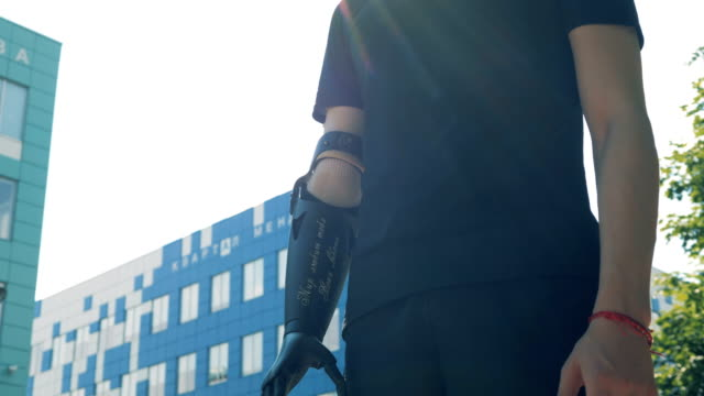 A-man-with-a-modern-bionic-prosthetic-arm-is-standing-in-city-Future-concept-
