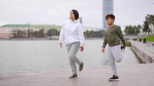 Asiatische-Mutter-und-Sohn-tun-Stretching-Ãœbung-auf-urban-Riverside-Sidewalk