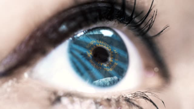 Woman-blue-eye-in-close-up-with-the-flag-of-South-Dakota-state-in-iris-united-states-of-america-with-wind-motion-video-concept