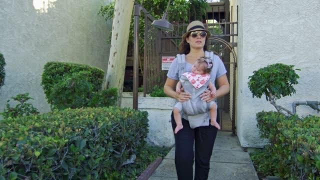 Frau-kommt-aus-dem-Gebäude-mit-schlafendem-Baby-auf-Träger