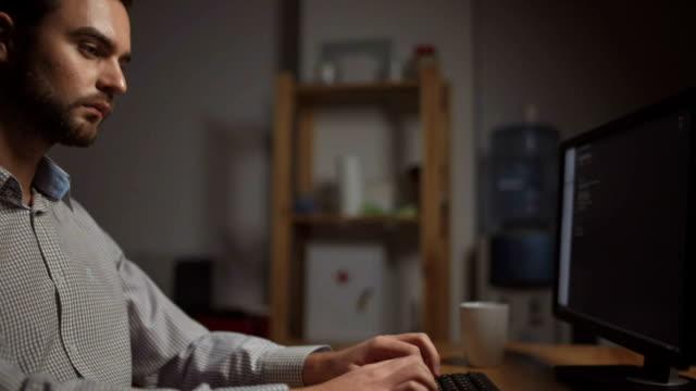 Serious-software-developer-writing-a-programming-code-at-night