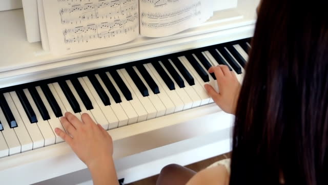 Young-brunette-is-playing-the-piano-in-bright-room