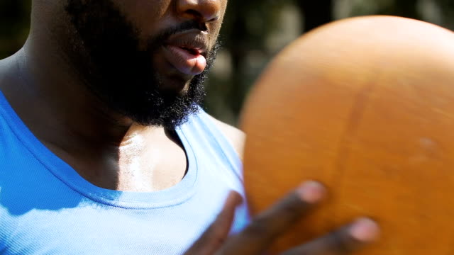 Concentrated-black-man-sighs-preparing-for-throw-on-basketball-court-sports
