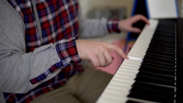 Manos-de-los-hombres-juegan-en-el-sintetizador-electrónico
