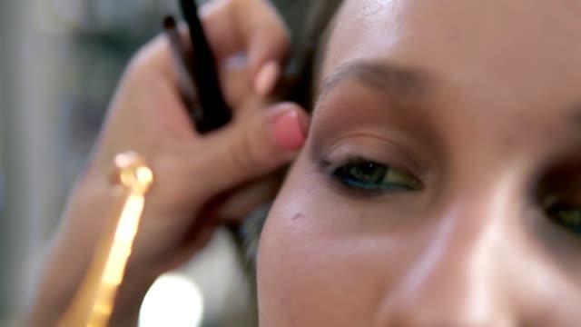 Augen-Make-up-Prozess-Künstler-korrigiert-augenlinie-mit-einem-professionellen-Pinsel-mit-goldenen-Rand-Nahaufnahme-von-einer-Modellfläche