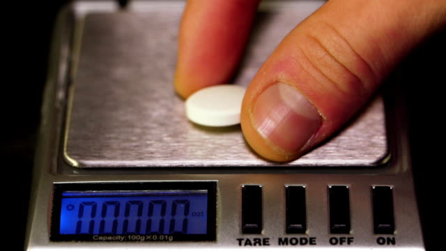 Pharmacist-puts-a-pill-on-the-scales-Pharmacist-weighs-the-manufactured-tablets-on-the-control-scales-Diet-pills-on-a-scale-Weight-loss-medicine-spilled