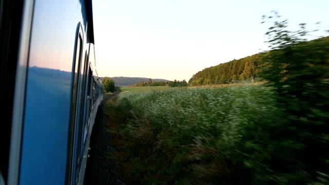 que-se-inclina-por-ventana-de-tren-en-el-bonito-campo-en-frente