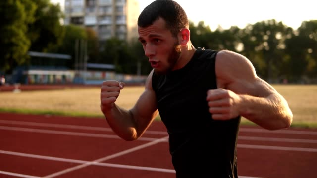 Accelerated-footage-of-a-male-boxer-while-training-process-on-the-outdoors-stadium-Portrait-of-a-man-boxing-with-invisible-opponent-punching-Side-view