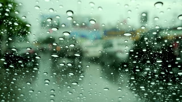 Car-windshield-with-rain-drops-during-heavy-traffic-downtown