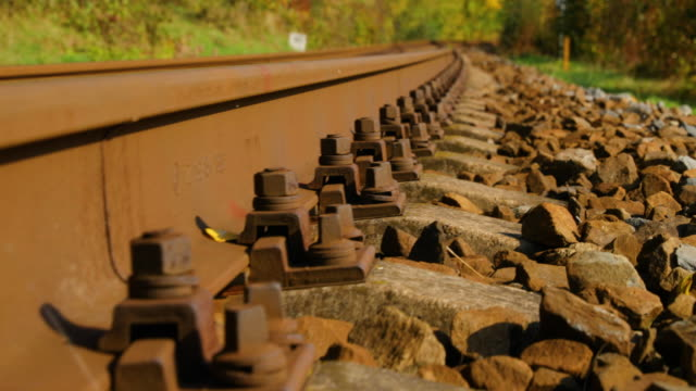 Slow-Close-up-view-of-security-bolts-at-train-tracks-in-slow-camera-movement-forward-outside-the-city-during-a-sunny-day-in-autumn-