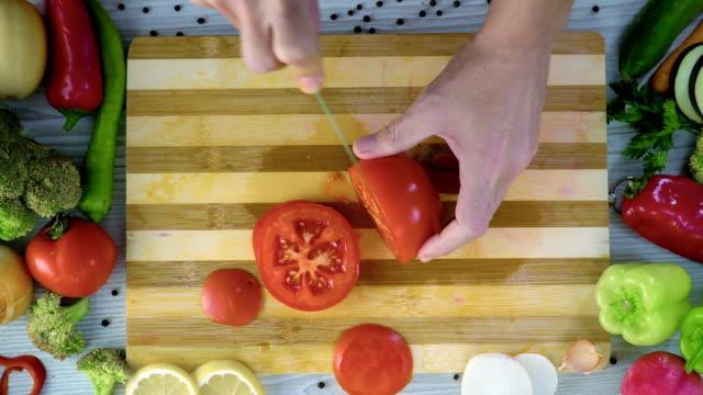 El-hombre-es-vegetales-de-corte-en-la-cocina-cortar-tomate