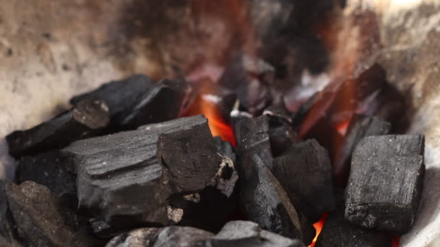 Licking-flame-from-fire-charcoal-in-thai-traditional-stove-with-pine-stick