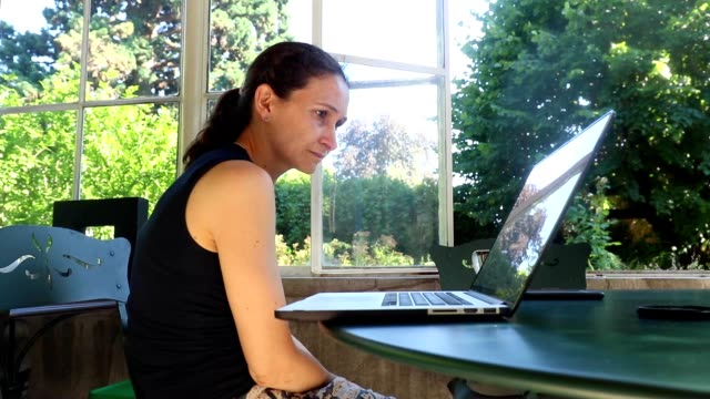 Mujer-en-su-computadora-portátil-leyendo-un-artículo-en-Internet-Madre-despertando-de-su-casa-balcón-