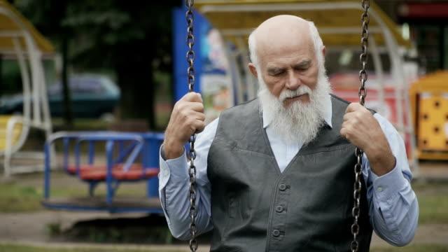 Sad-old-man-swings-on-seesaw-in-slowmotion