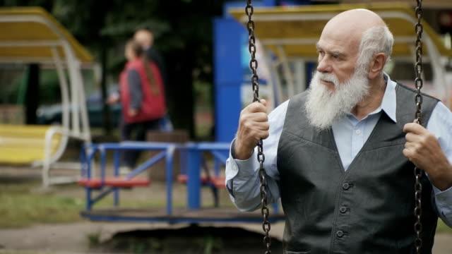 Gloomy-grey-haired-old-man-swings-in-slowmotion