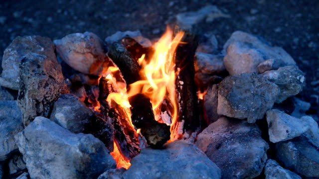 Bonfire-in-a-camp-fire-of-stones-outdoors-at-dusk