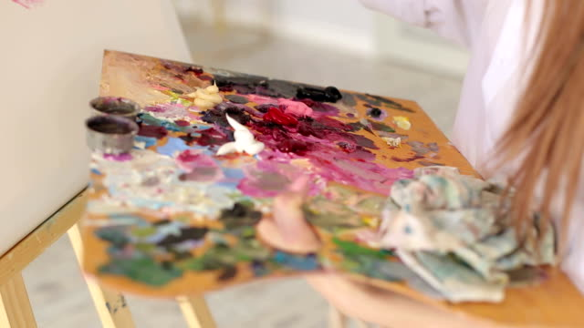 Artist-mixes-oil-paints-on-a-palette-with-a-brush-
