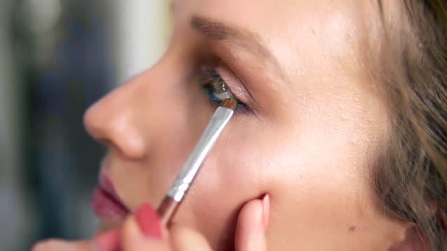 Seitlicher-Blick-auf-einer-Modellfläche-Make-up-Artist-Lidschatten-unter-dem-unteren-Augenlid-mit-Pinsel-auftragen-Blauen-Eyeliner-Prozess-machen