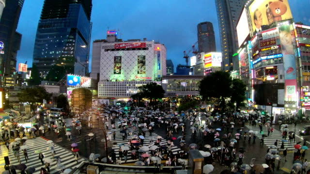 4K-Time-lapse-video-of-people-with-umbrellas-cross-the-famous-diagonal-intersection-in-Shibuya-Tokyo-Japan