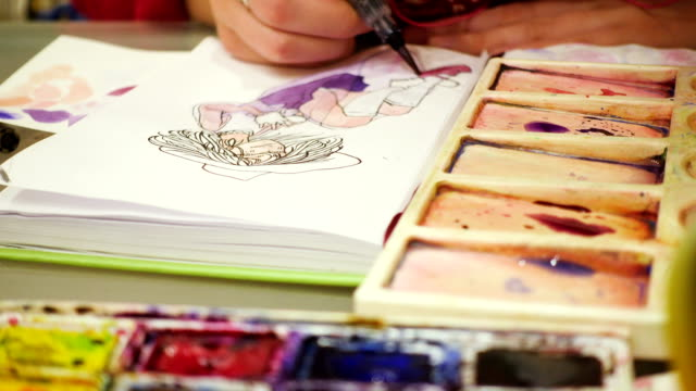 artist-drawing-a-sketch-with-the-watercolors-paints