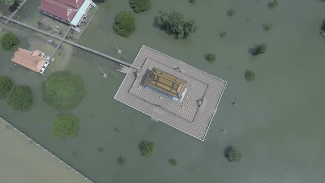 Locked-overhead-drone-shot-of-a-pagoda-is-surrounded-by-floodwaters