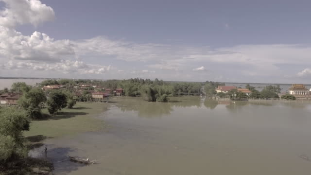 aerial-drone-shot:-fly-towards-a-sleepy-village-surrounded-by-floodwaters