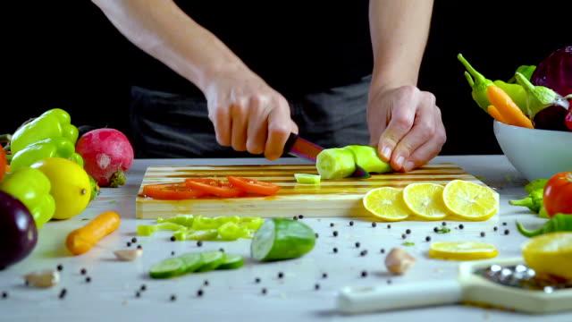 El-hombre-es-vegetales-de-corte-en-la-cocina-rebanando-pepino