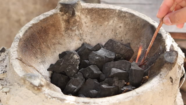 Firing-charcoal-in-thai-traditional-stove-with-pine-stick
