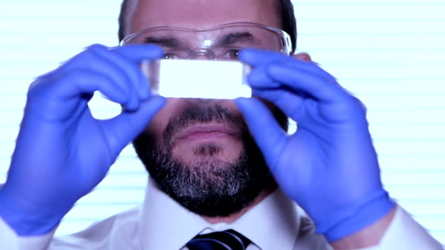 Biologist-examines-sample-Science-biology-ecology-Professional-scientist-wearing-protective-mask-working-with-herb-samples-in-his-laboratory-Male-scientist-looking-at-plant-leaf-in-glass-slide-