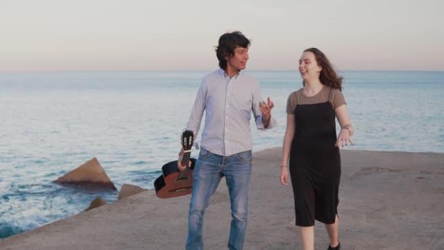 Beautiful-musician-couple-walk-walk-along-the-pier-by-the-sea