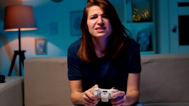 La-chica-triste-pierde-el-videojuego-en-casa-por-la-noche-Mujer-jugadora-excitada-sentada-en-un-sofá-jugando-y-perdiendo-en-videojuegos-en-una-consola-usando-un-mando-inalámbrico-Habitación-acogedora-ambiente-casero-encantador