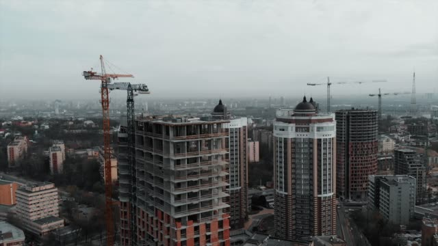 Group-of-caucasian-workers-in-orange-helmets-working-on-roof-of-unfinished-building-Workers-at-construction-of-high-rise-residential-complex
