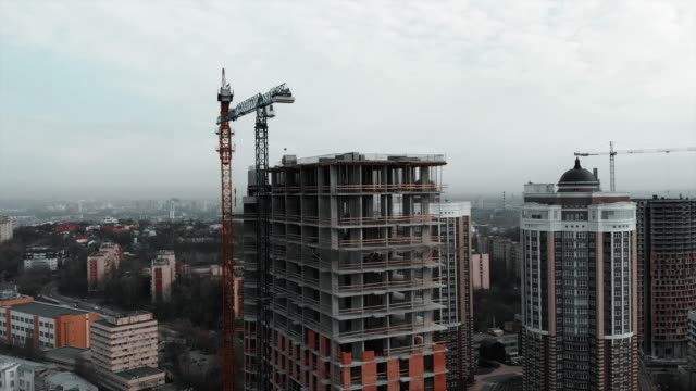 Brick-and-concrete-at-construction-works-Aerial-drone-view-of-high-rise-residential-complex-construction-High-crane-near-unfinished-building