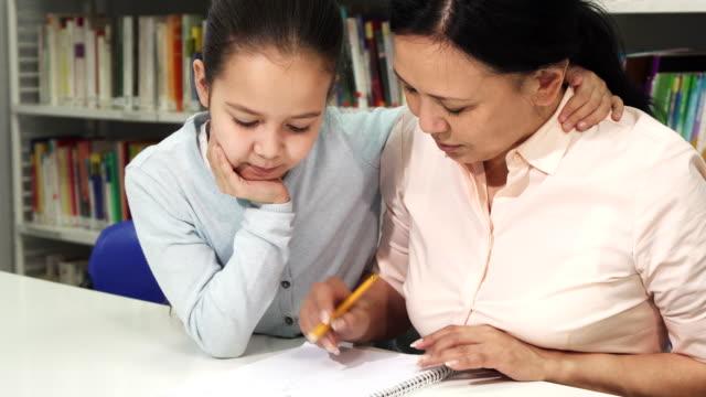 Mujer-asiática-madura-feliz-ayudando-a-su-hijita-con-el-estudio-de