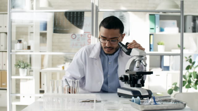 Focused-Black-Scientist-Using-Microscope