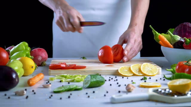 El-hombre-es-vegetales-de-corte-en-la-cocina-cortar-el-tomate-en-cámara-lenta