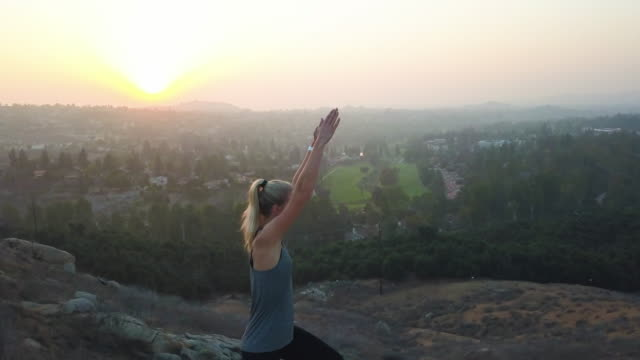 Strong-beautiful-woman-yoga-fitness-in-nature-sunset-aerial