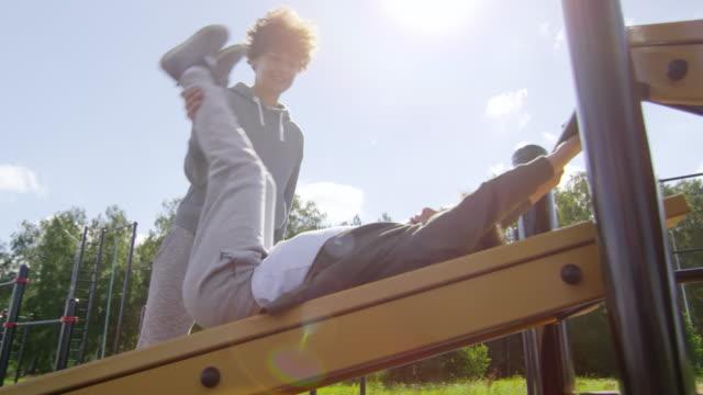 Mother-Teaching-Little-Son-to-Do-Leg-Raises-on-Outdoor-Workout-Playground