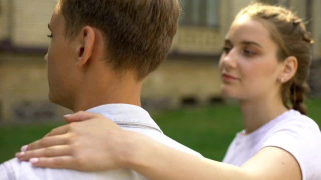 Sad-teen-girlfriend-hugging-boyfriend-and-looks-at-camera-relation-difficulties