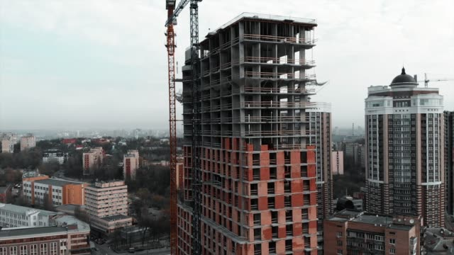 Construction-crane-at-construction-site-Construction-of-brick-concrete-residential-building-aerial-drone-view-Unfinished-high-rise-house