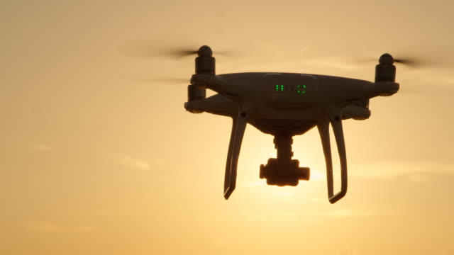 SLOW-MOTION-CLOSE-UP-SILHOUETTE:-Drone-flying-towards-the-sun-at-golden-sunset