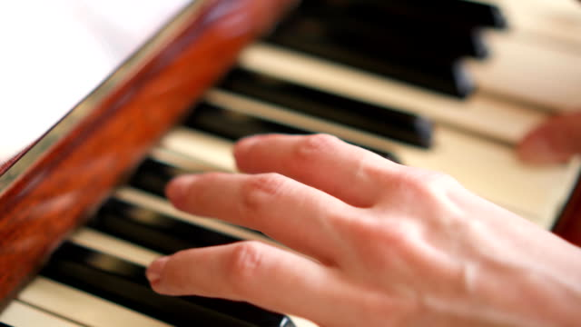 Female-fingers-playing-keys-on-retro-piano-keyboard-Shallow-depth-of-field-Focus-on-hands