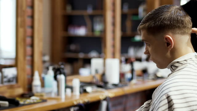 Professional-barber-makes-modern-hairstyle-for-young-caucasian-guy