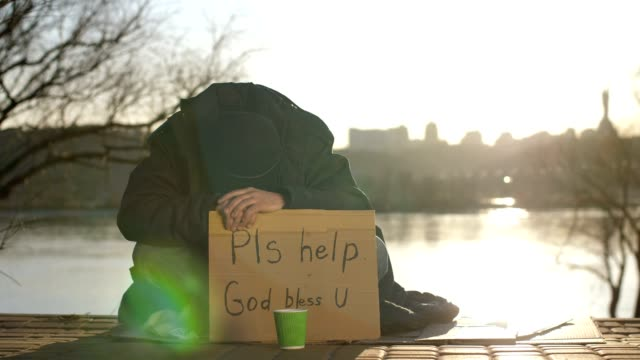 Sad-beggar-sitting-with-head-down-asking-for-help