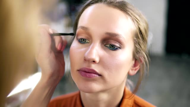 Overview-of-a-make-up-process-Professional-make-up-artist-gently-putting-nude-eyeshadows-on-an-eyelid-Attractive-young-blonde-model