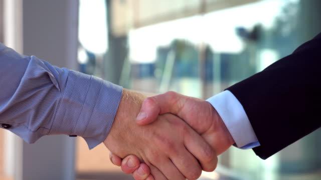 Cerca-de-dos-empresarios-exitosos-saludándose-en-entorno-urbano-Jóvenes-colegas-reunión-y-agitando-las-manos-cerca-de-edificio-de-oficinas-Apretón-de-manos-de-los-socios-comerciales-al-aire-libre-Vista-lateral