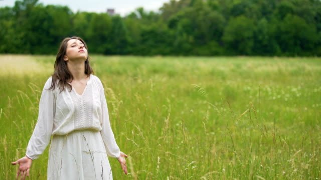 Woman-enjoys-connection-with-nature-open-hands-towards-wheat-field-oneness