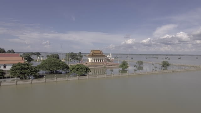 Aerial-static-view-of-a-pagoda-is-surrounded-by-floodwaters-under-cloudy-skies