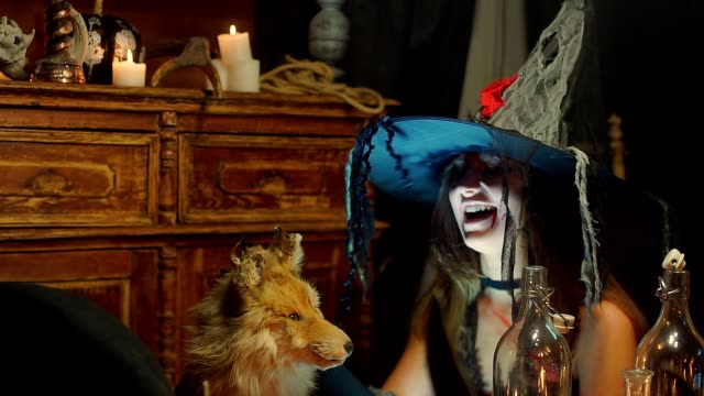 Halloween-witch-strokes-a-dead-fox-and-laughs-maliciously-